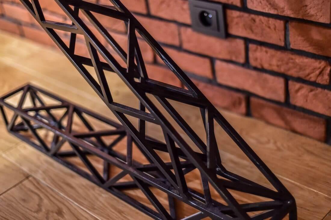 Czarne metalowe industrialne nogi stołu na parkiecie i ceglanej ścianie z gniazdkiem