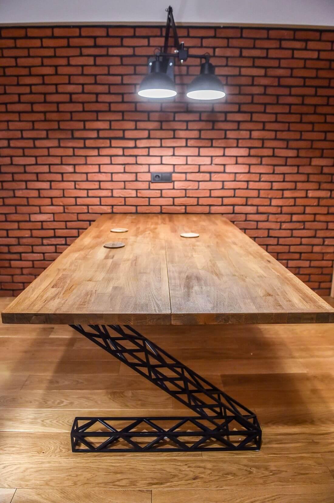 Stół Industrialny drewniany prostokątny z metalowymi nogami oświetlony z góry na ceglanej ścianie