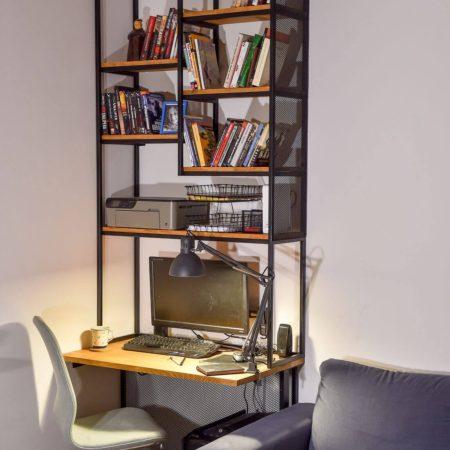 Biurko Industrialne z Regałem do sufitu wykonanym z metalu i drewna – książki na półkach oraz monitor na biurku