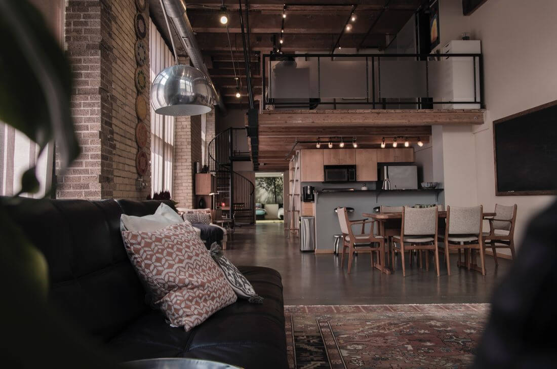 Loft apartment with mezzanine, curved metal stairs, high spacious windows and brick walls