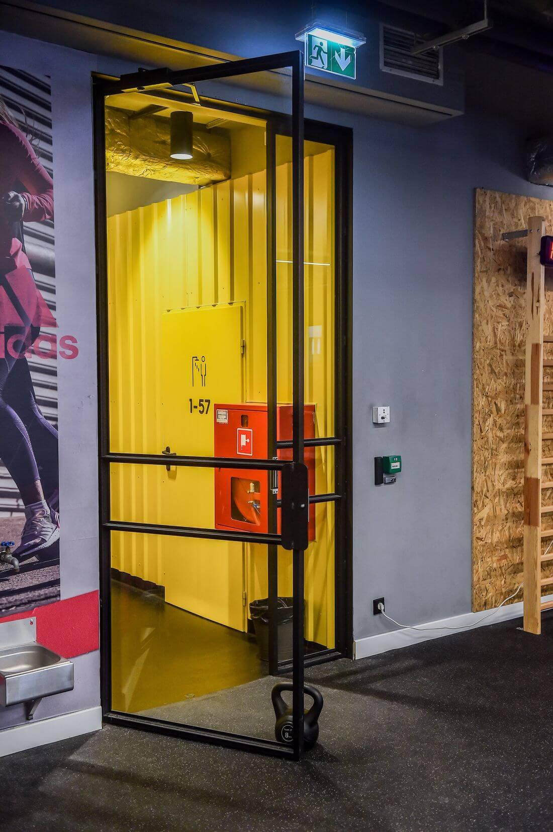Drzwi Loftowe i Ściany Loftowe Przeszklone Czarne Metalowe otwarte w Adidas Runners Warsaw w żółtym korytarzu