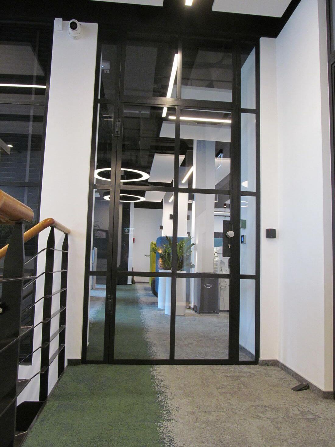 Drzwi Loftowe Czarne Metalowe w biurze EIP wraz z industrialną przeszkloną ramą otaczającą drzwi