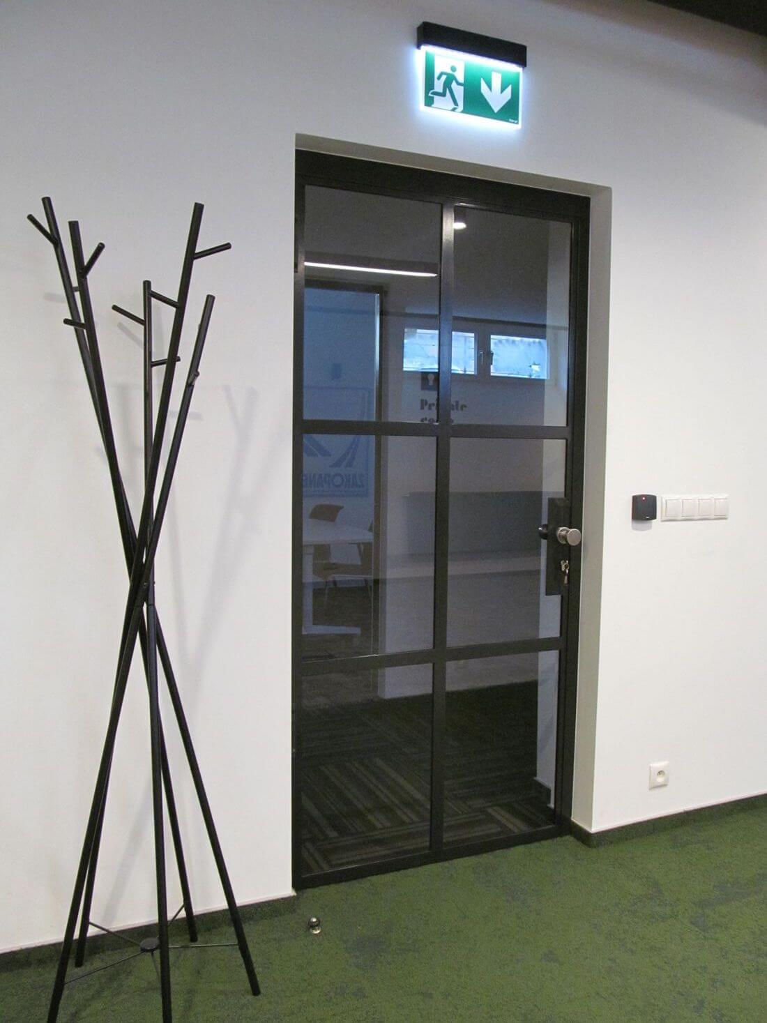Drzwi Loftowe Industrialne Uchylne w biurze EIP Group wykonane ze szkła wzmacnianego 33.1 wraz z folią zabezpieczającą