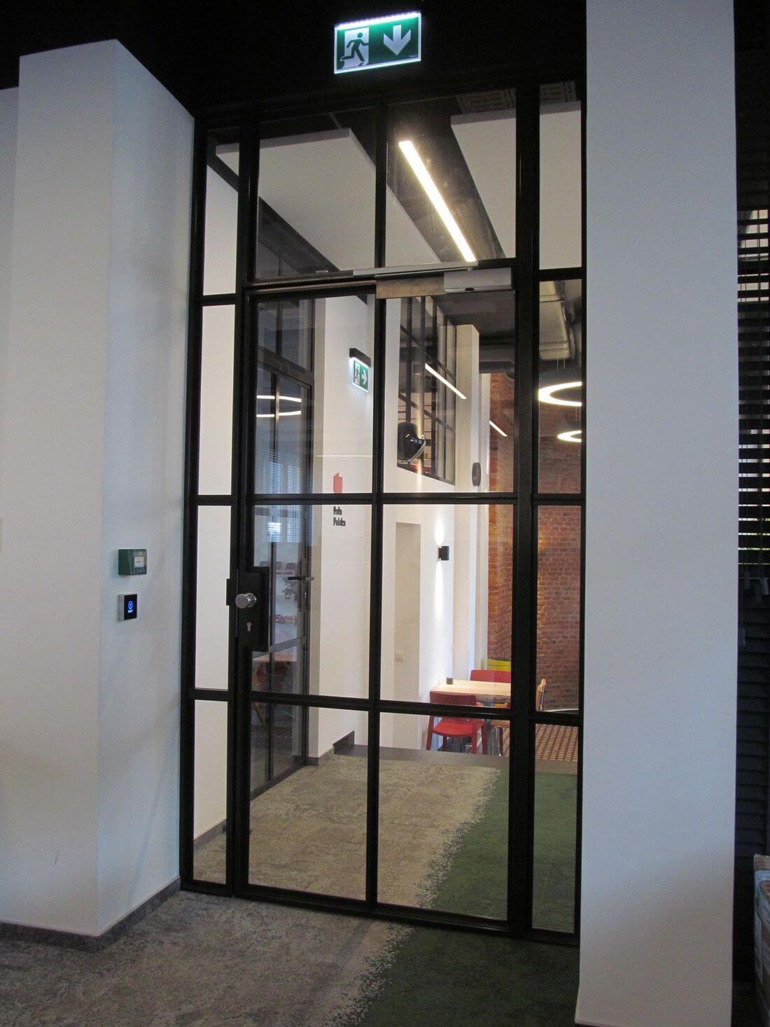 Drzwi Loftowe Industrialne Uchylne Szklane przezroczyste w biurze EIP z przeszkloną ramą otaczającą drzwi