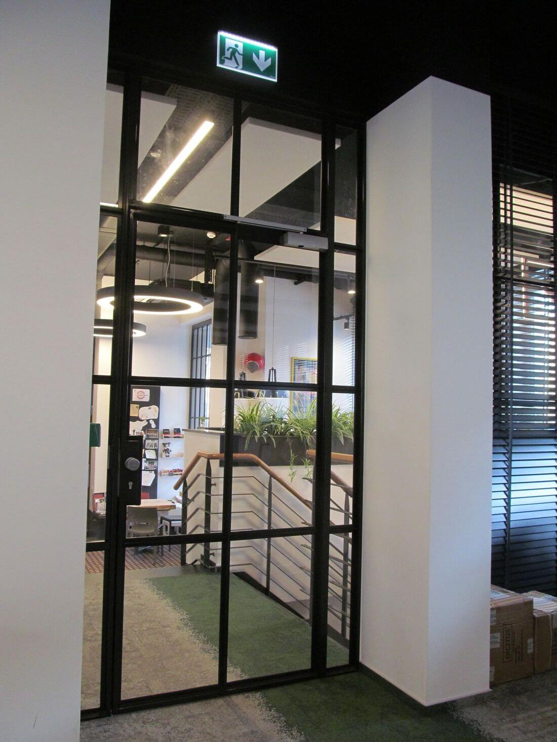 Industrial Tilting Loft Doors from Glass Transparent in EIP Warsaw office with glass frame
