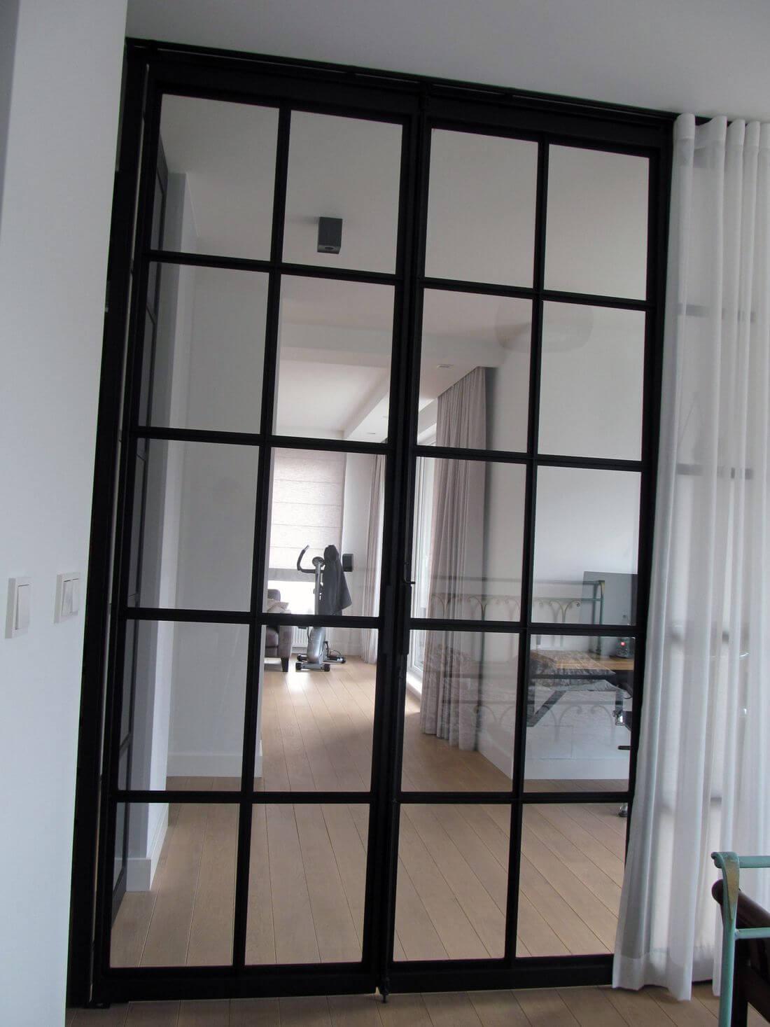 Drzwi Loftowe Industrialne wychodzące z sypialni do pokoju dziennego zamknięte – wykonane ze szkła i metalu