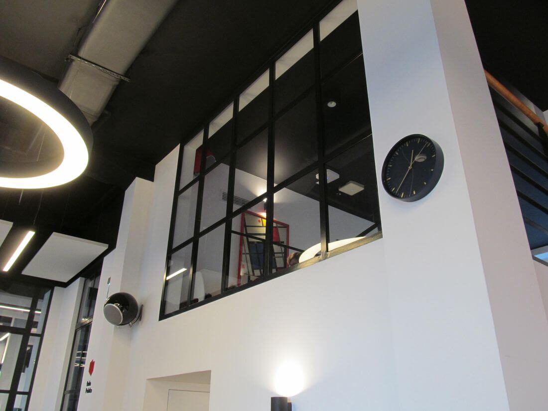 Loft wall system made of structural steel and reinforced glass 33.1 separating offices from the Charity café