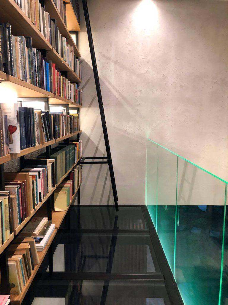 Szklana balustrada i metalowa drabina na antresoli metalowej loft z podłogą ze szkła hartowanego oraz biblioteką industrialną
