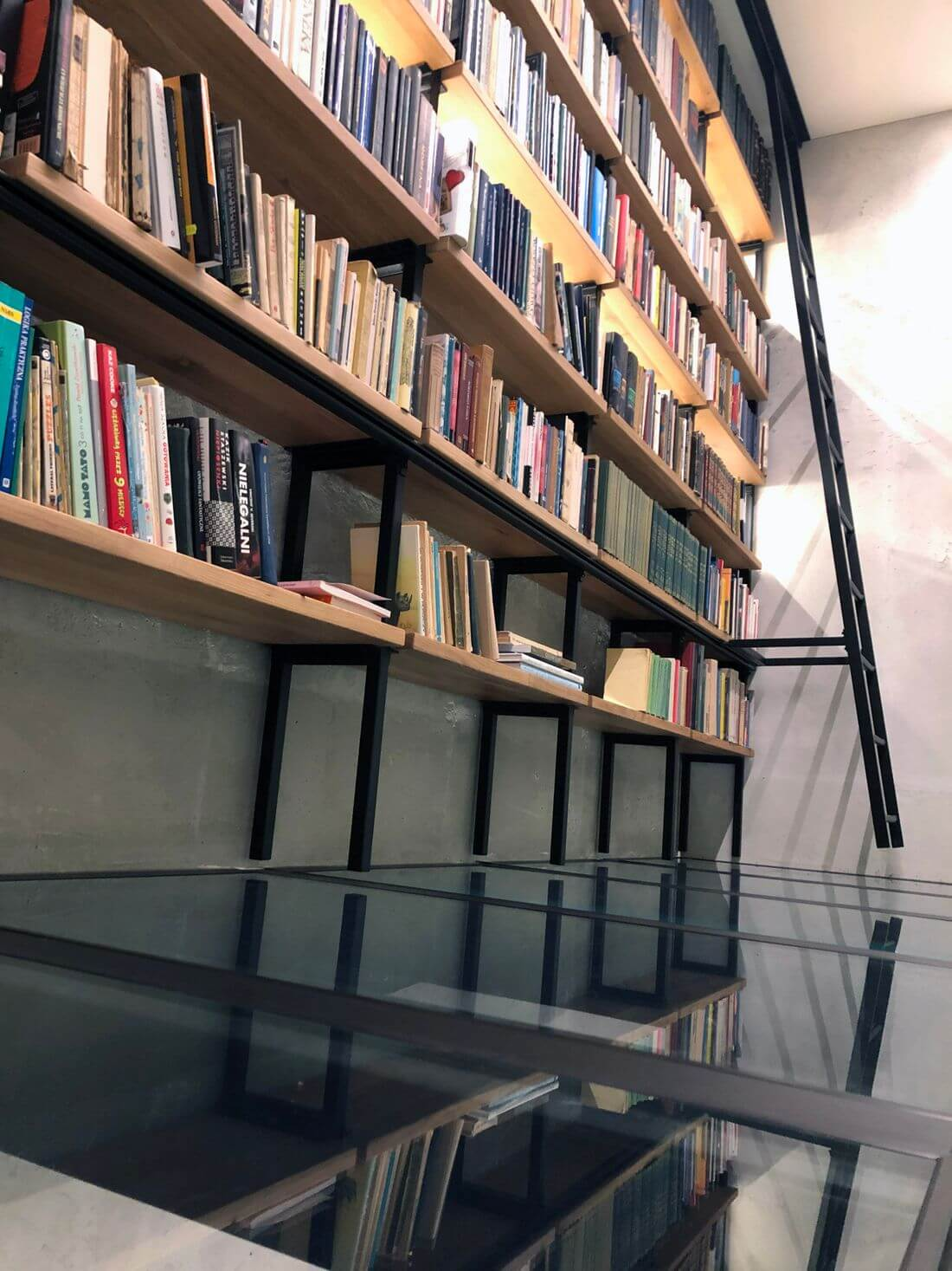 Tempered glass floor on the mezzanine with a library made in loft industrial style of structural steel