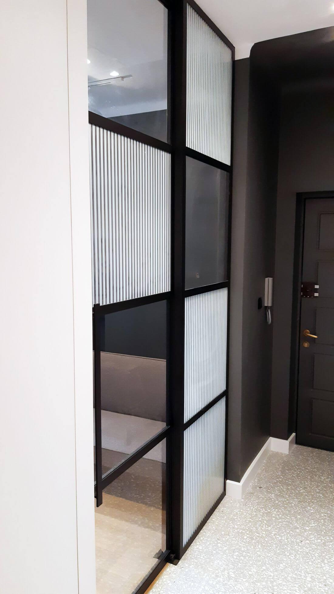 Drzwi rozsuwane loftowe ze szkła i metalu z szyną w suficie w przedpokoju pomalowanym na szaro
