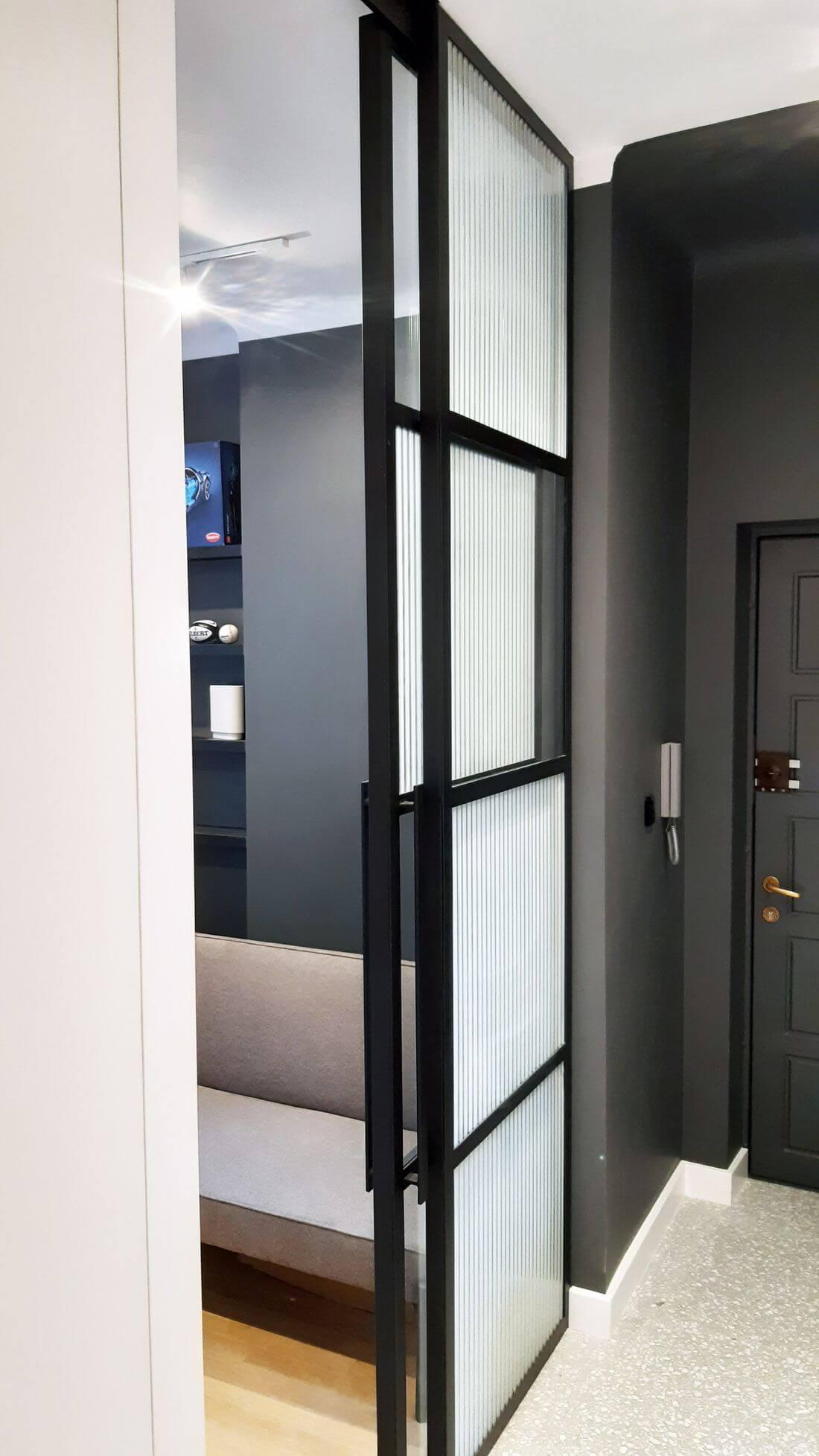 Drzwi rozsuwane loftowe otwarte ze szkła i metalu z szyną w suficie w przedpokoju z szarymi ścianami