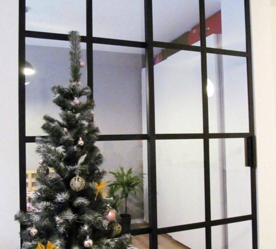 drzwi przesuwne loft do sypialni ze szkła zainstalowane w salonie z choinką oraz białymi ścianami