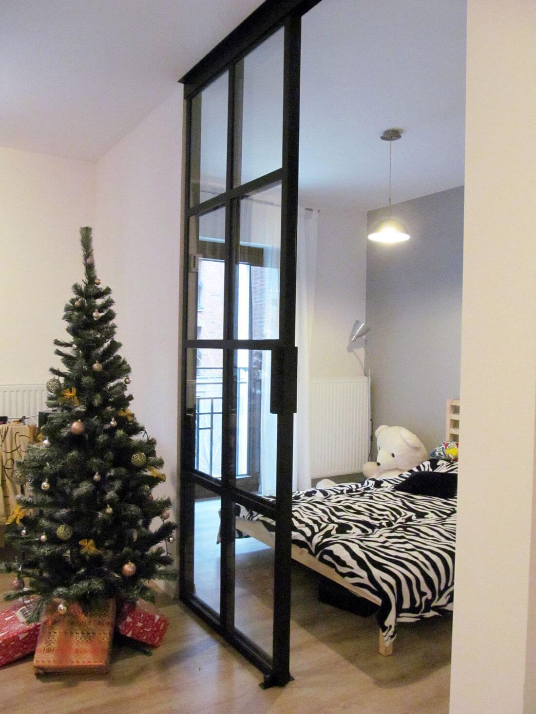 Otwarte drzwi przesuwne loftowe w przejściu z salonu do sypialni z choinką po lewej stronie – mieszkanie z białymi ścianami