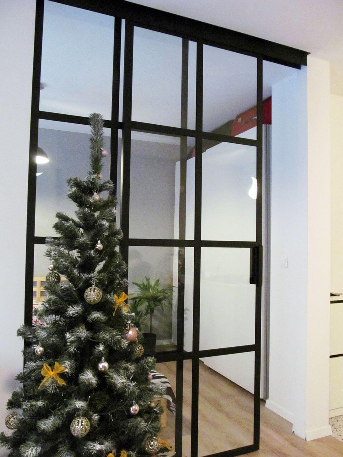 Do połowy otwarte drzwi przesuwne loftowe w przejściu z salonu do sypialni z choinką po lewej stronie – białe ściany