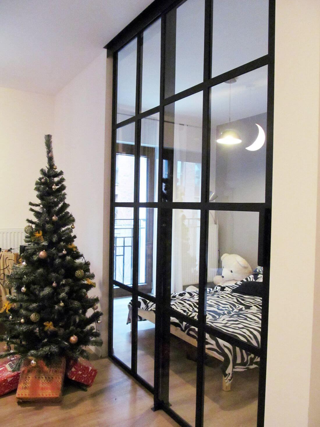 Wykonane z metalu i szkła drzwi przesuwne pomiędzy sypialnią i salonem oparte na szynie w suficie i prowadnicy na parkiecie