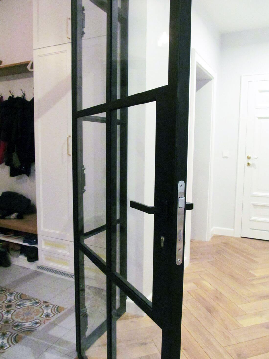 Handle with cylinder lock in loft door with industrial glazed wall made of structural steel