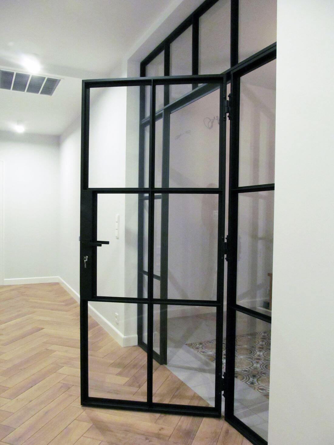 Loft glazed partition with swinging loft doors lit by artificial light from the corridor