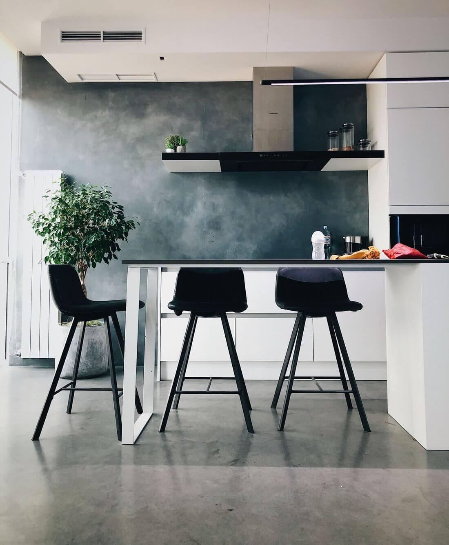 Kuchnia Industrialna w Stylu Loftowym z czarnymi wysokimi krzesłami, białymi meblami i betonową surową ścianą
