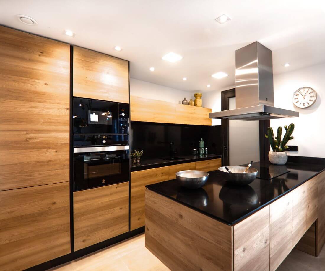kuchnia styl loftowy – drewniane półki – biały sufit – czarna wyspa z kuchenką i okapem – jasne światło