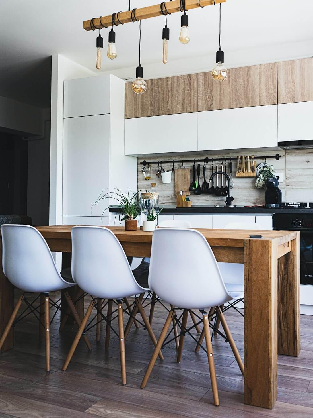 Kuchnia Loft w Stylu Industrialnym w mieszkaniu loftowym z drewnianym stołem, białymi krzesłami i wiszącymi żarówkami