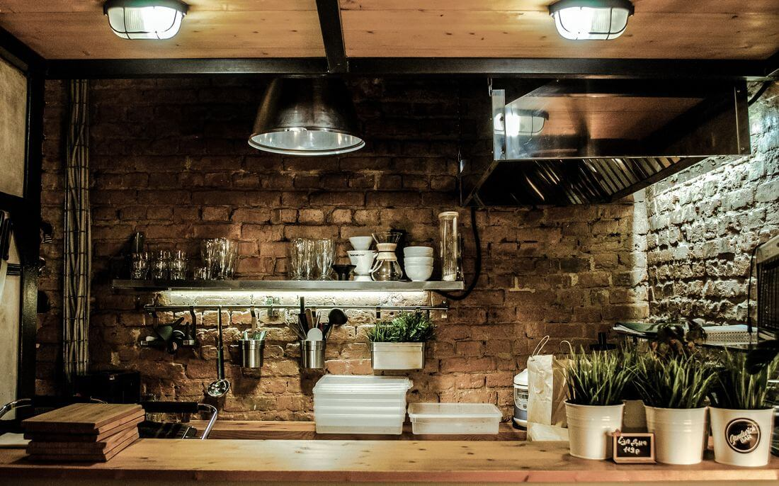 Kuchnia Rustykalna Loftowa z ceglaną ścianą, zielonymi doniczkowymi roślinami, metalowymi półkami, drewnianymi blatami