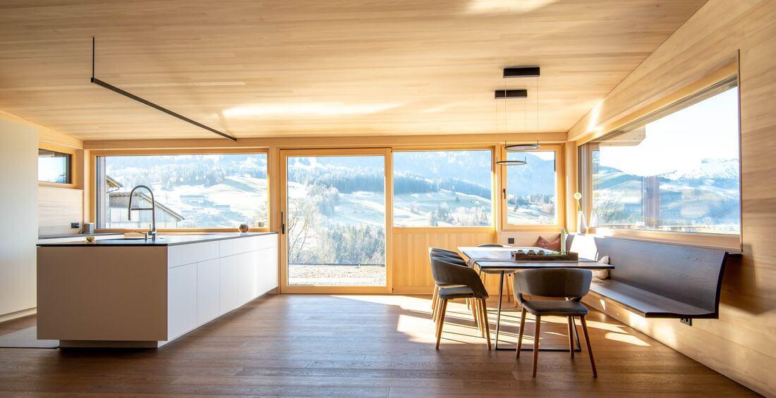 Kuchnia Loftowa w górskim domu z wyspą i drewnianym industrialnym stołem – kuchnia industrialna z dużymi oknami