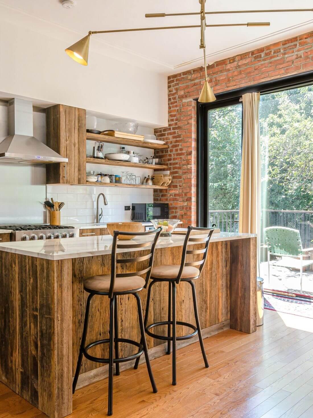 Kuchnia Loftowa w Stylu Industrialnym w apartamencie loftowym z ceglaną ścianą, drewnianymi meblami oraz drzwiami loftowymi