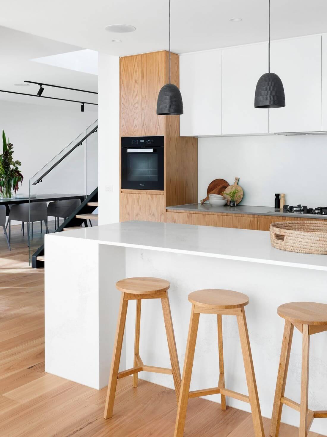Kuchnia Loftowa w stylowym białym jasnym designie z drewnianymi hookerami barowymi i stylowymi czarnymi wiszącymi lampami