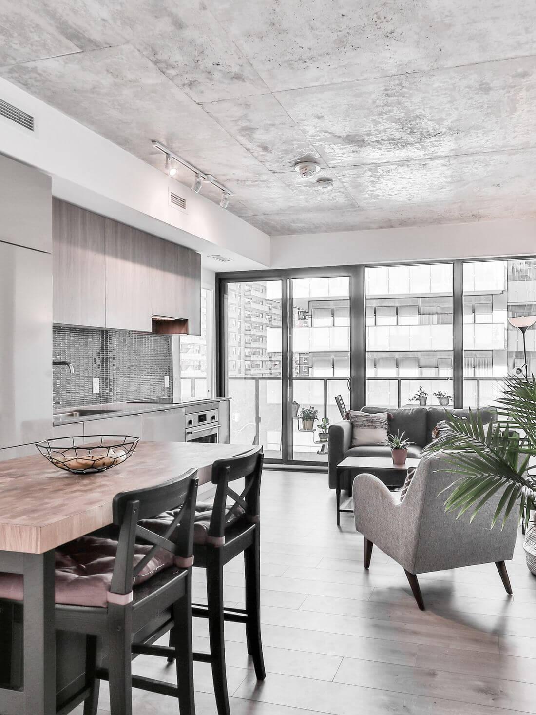 Kuchnia w Stylu Loftowym z wysokim sufitem z betonu, drzwiami loftowymi, stołem z drewnianym blatem i metalowymi nogami