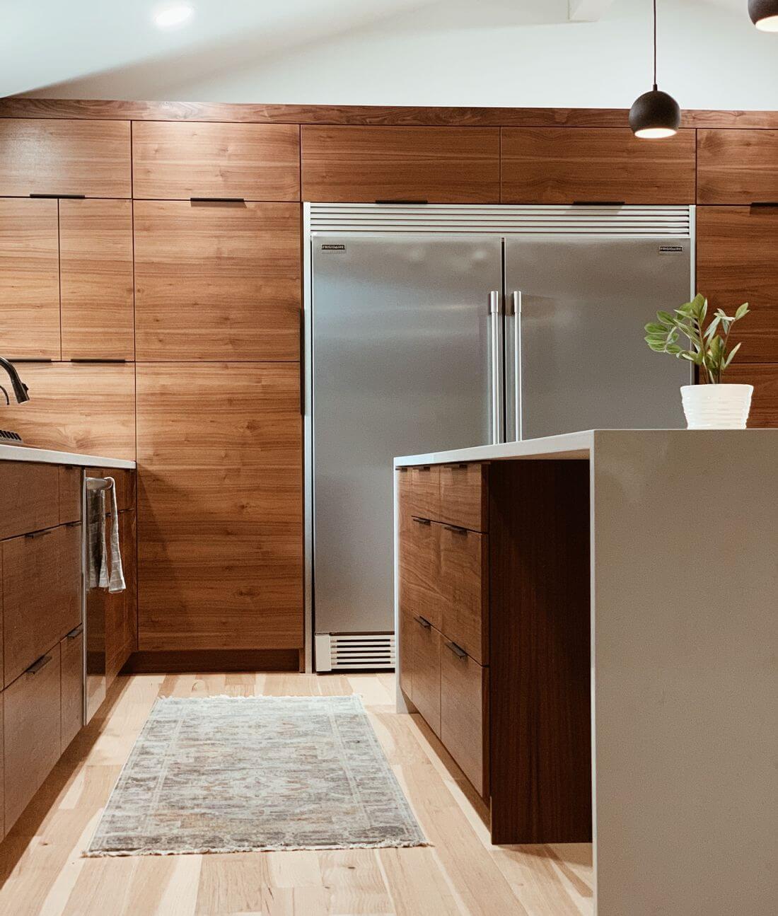 Drewniane Brązowe Półki i szafki w kuchni loftowej lodówka zamrażalnik z metalowymi drzwiami wyspa na środku kuchni loftowej