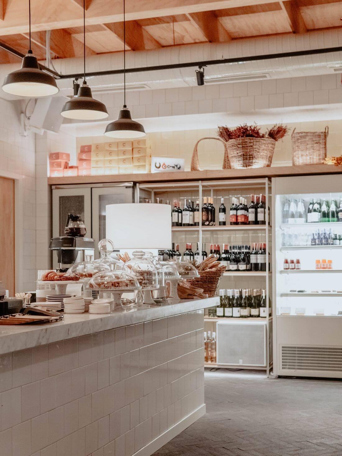 Spiżarnia w Kuchni Loftowej z lodówkami oraz metalowymi półkami – kawiarnia loftowa z ladą, rogalikami, ciastkami i pieczywem