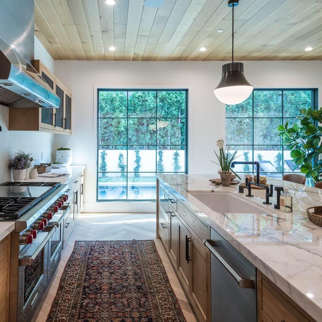 Styl Loftowy Kuchnia z Wyspą na środku z oknami i drzwiami loftowymi z dywanem na podłodze i rośliną zieloną
